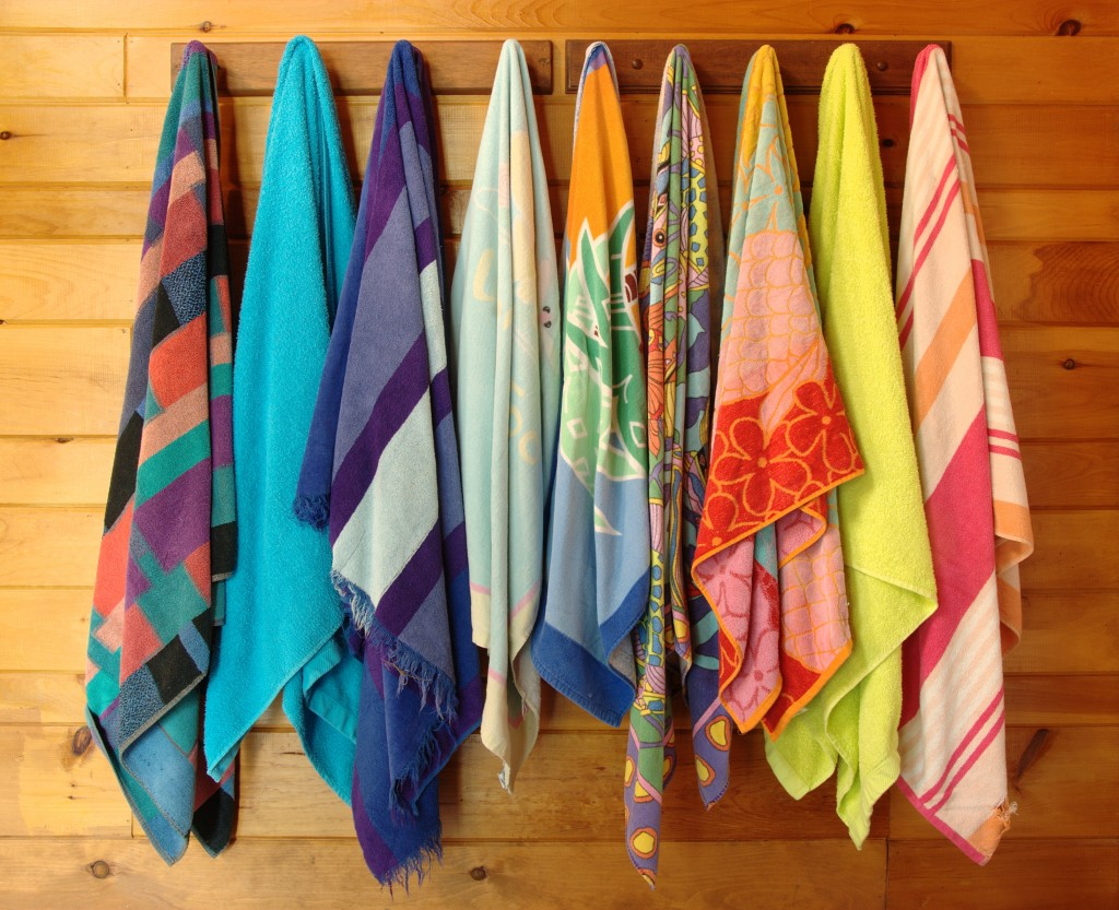 Multicolored patterned beach towels hanging on a wood wall