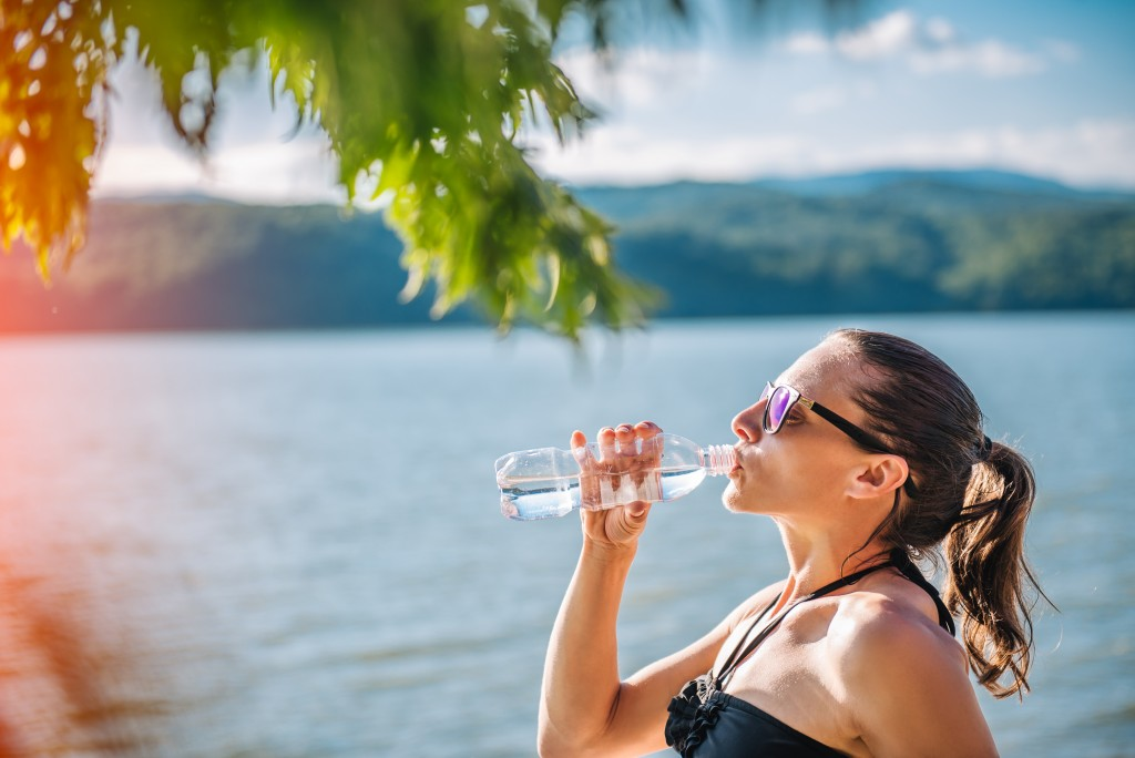 Woman drinking water from PET bottle