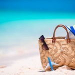 Beach accessories - straw bag, headphones, toy plane and sunglasses